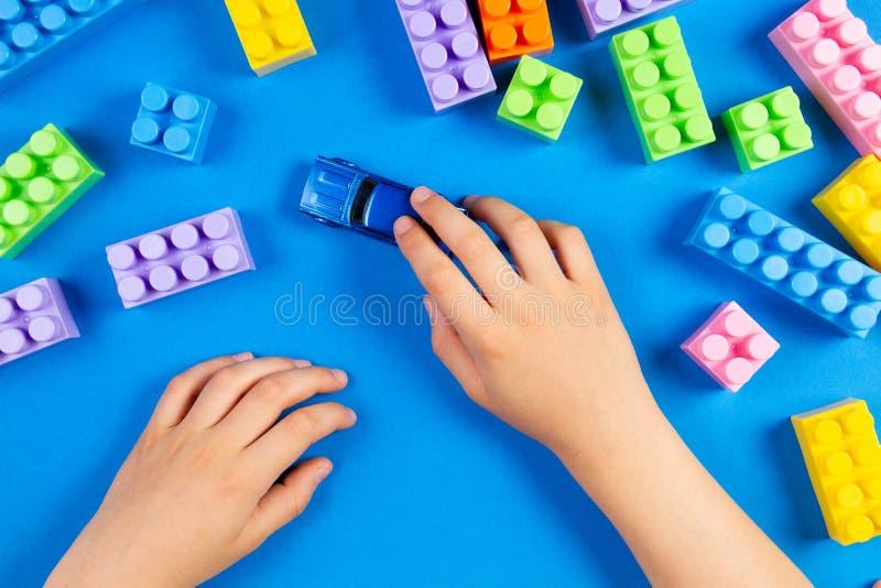 Los niños dan jugar con los bloques plásticos coloridos de la construcción del coche del juguete alrededor en fondo azul imágenes de archivo libres de regalías