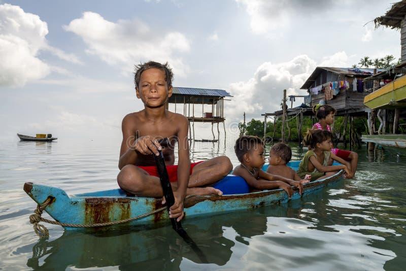 Los niños de Bajau se relajan en excavado un barco cerca de línea de la playa en Sabah, Malasia imágenes de archivo libres de regalías