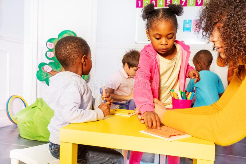 Los niños de la clase de guardería abotonan con el profesor fotos de archivo libres de regalías