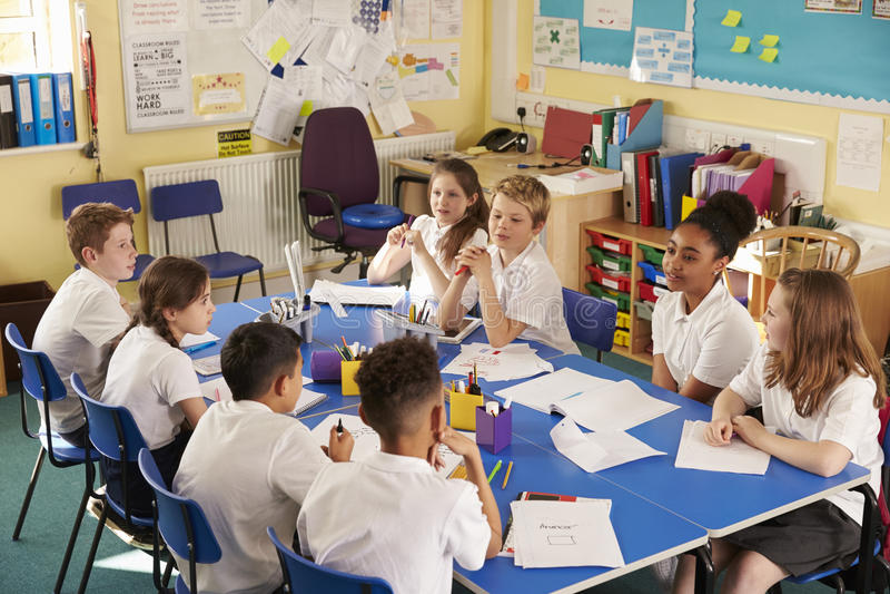 Los niños de la escuela trabajan juntos en un proyecto de la clase, visión elevada foto de archivo