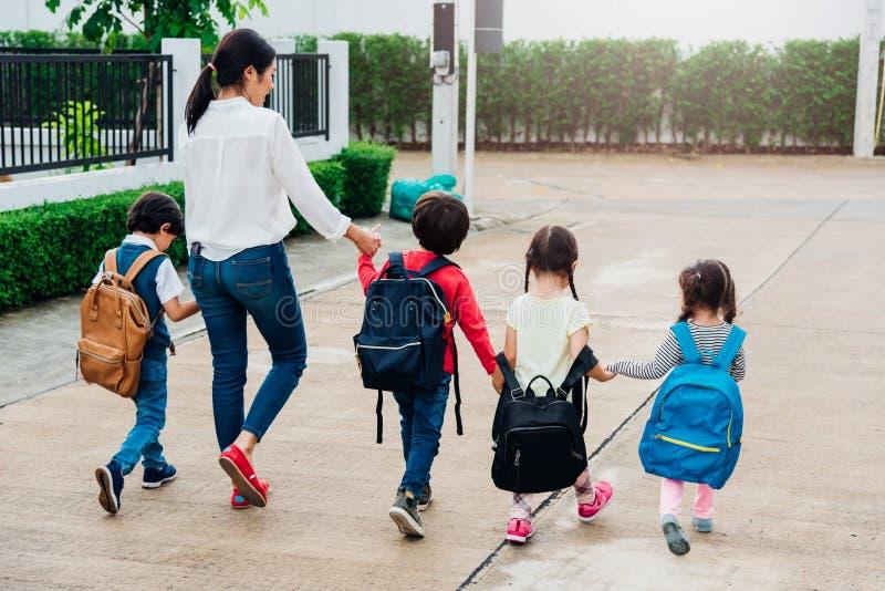 Los niños de la familia embroman ir que camina de la guardería de la muchacha y del muchacho del hijo fotografía de archivo