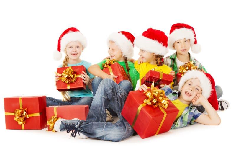 Los niños de la Navidad en la tenencia del sombrero de Papá Noel presentan la caja de regalo roja foto de archivo libre de regalías