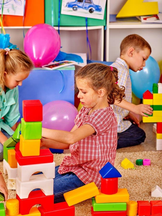 Los niños del grupo juntos están jugando con los bloques en guardería fotografía de archivo