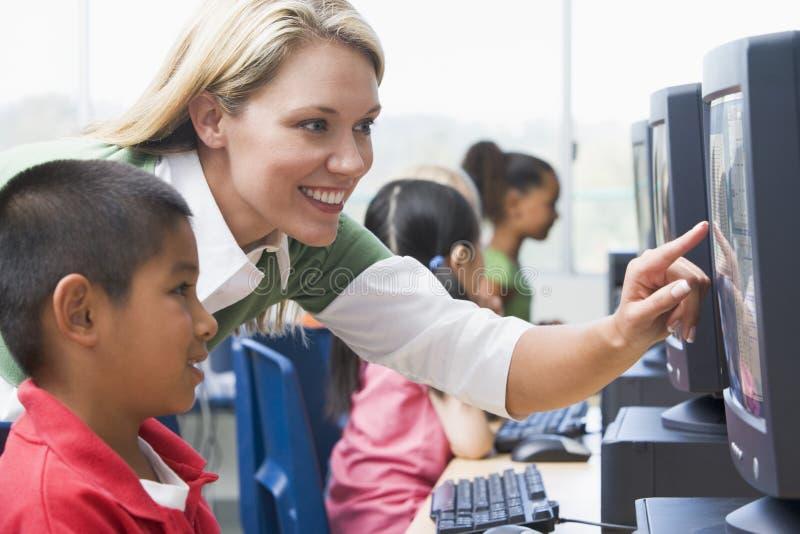 Los niños del jardín de la infancia aprenden utilizar el ordenador fotografía de archivo libre de regalías