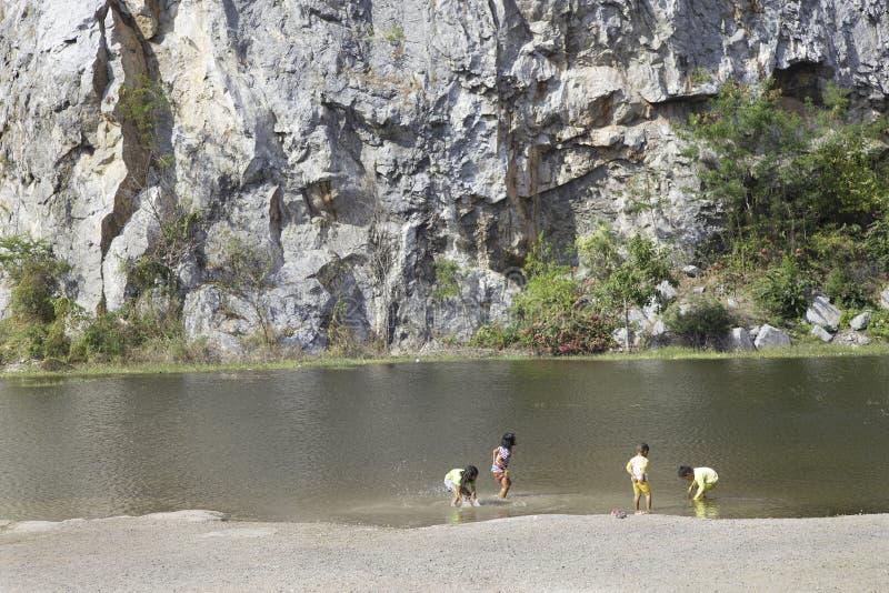 Los niños del muchacho y de la muchacha juegan al lado de la diversión del lago fotografía de archivo libre de regalías