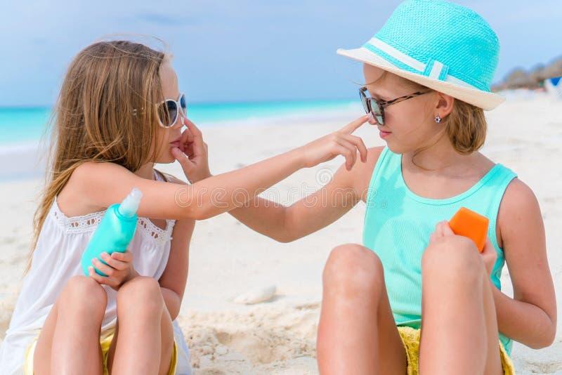 Los niños del primer dos toman el cuidado de uno a Niños que aplican la crema del sol el uno al otro en la playa El concepto de p imágenes de archivo libres de regalías