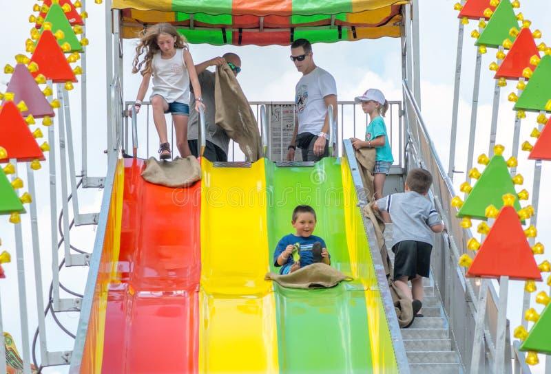Los niños deslizan abajo una diapositiva gigante imagen de archivo libre de regalías
