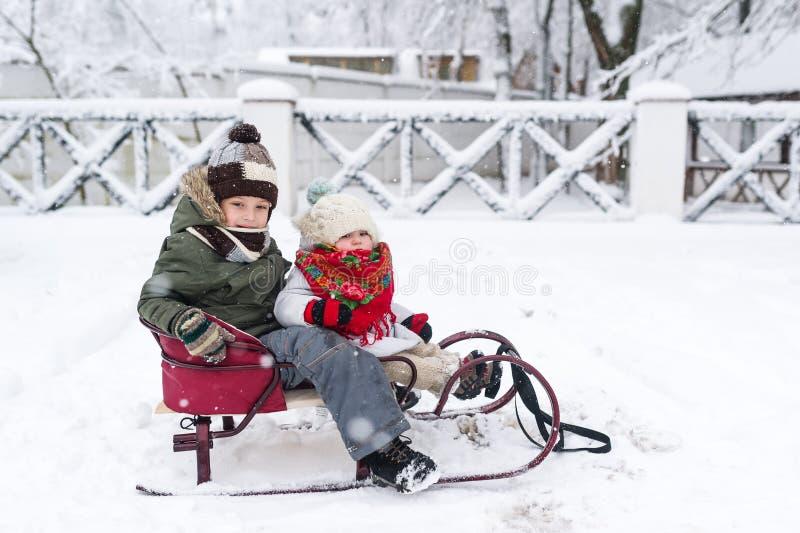 Los niños disfrutan de un paseo del trineo El sledding del niño Juego de niños al aire libre en nieve fotos de archivo