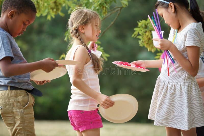 Los niños distribuyen las placas en un partido imagen de archivo libre de regalías
