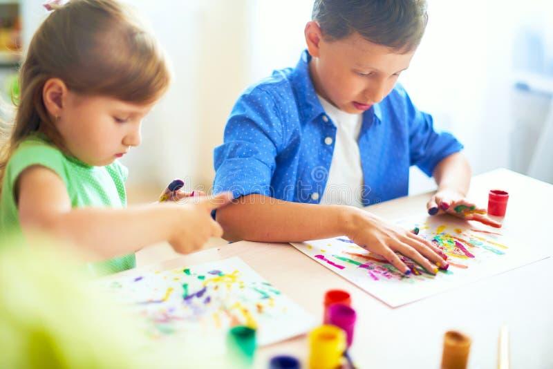 Los niños divertidos muestran a sus palmas la pintura pintada bellas arte creativas de las clases dos niños un muchacho y una ris foto de archivo