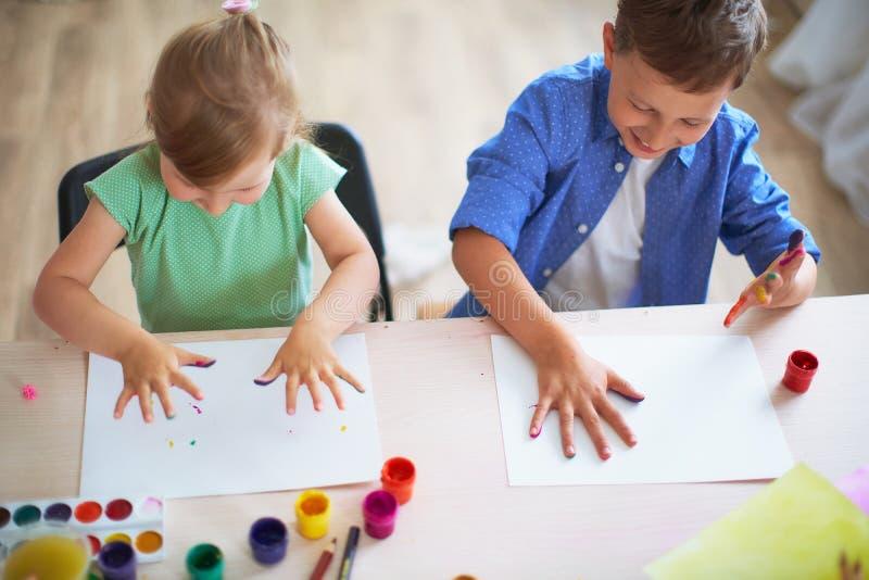Los niños divertidos muestran a sus palmas la pintura pintada bellas arte creativas de las clases dos niños un muchacho y una ris imágenes de archivo libres de regalías