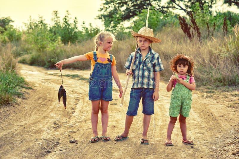 Los niños divertidos van a pescar por la tarde del verano en un camino de tierra foto de archivo