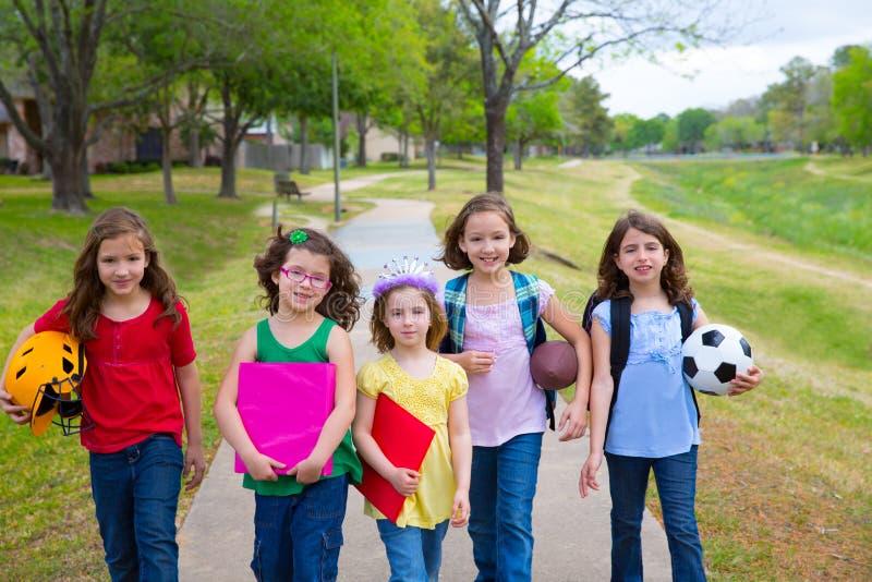 Los niños embroman a las muchachas que caminan al schoool con las bolas del deporte imagen de archivo libre de regalías