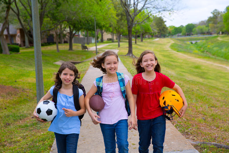 Los niños embroman a las muchachas que caminan al schoool con las bolas del deporte fotos de archivo libres de regalías
