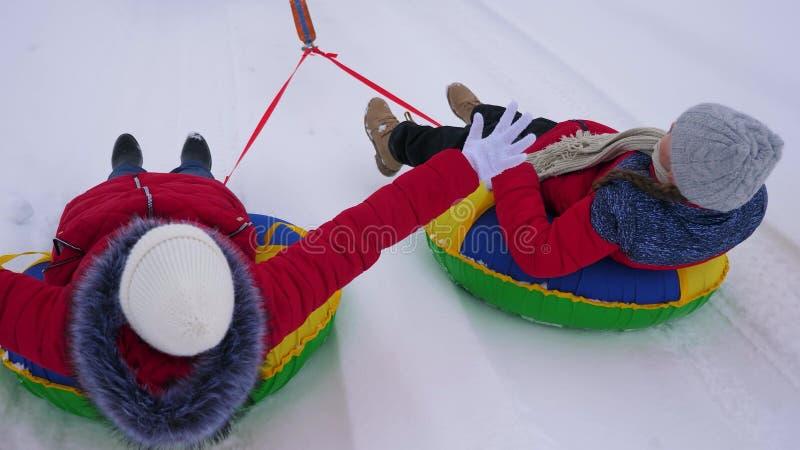 Los niños en chaquetas rojas montan a través de nieve en invierno en un tubo inflable de la nieve y superhéroes del juego Muchach fotos de archivo