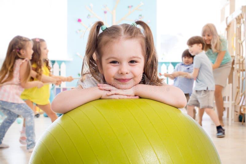 Los niños en el gimnasio Niña en edad preescolar con equipo físico en la enseñanza de educación física foto de archivo
