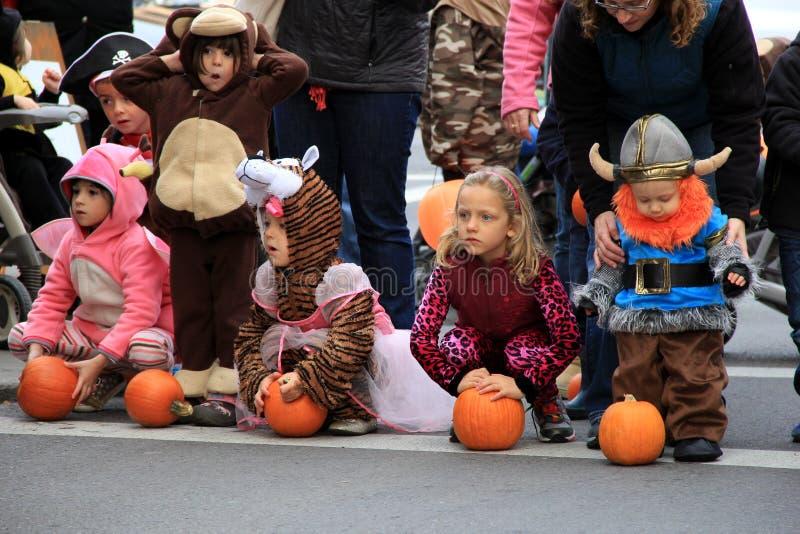 Los niños en el traje que espera a la calabaza ruedan abajo de Caroline Street, octubre de 2013, Saratoga Springs, Nueva York foto de archivo