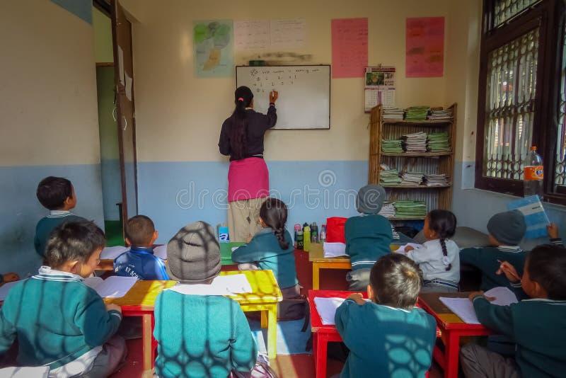Los niños en la sala de clase, profesor escriben en el whiteboard, Katmandu, Nepal fotografía de archivo