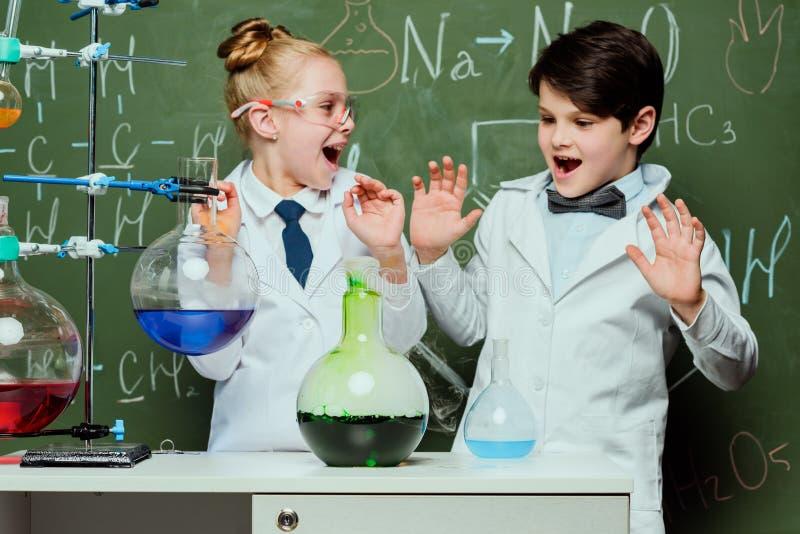 Los niños en las capas blancas con la pizarra detrás en el laboratorio, niños de los científicos combinan concepto fotos de archivo