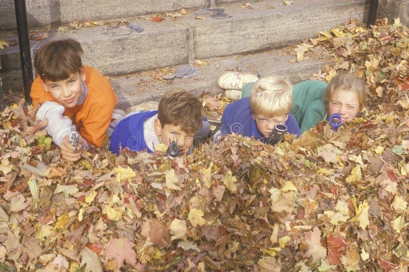 Los niños en las hojas de otoño que apuntan el juguete disparan contra, Westpoint, NY imágenes de archivo libres de regalías