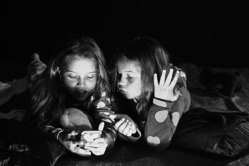 Los niños en pijamas miran película en el teléfono en fondo oscuro Concepto del partido y de la diversión Las colegialas tienen p imágenes de archivo libres de regalías