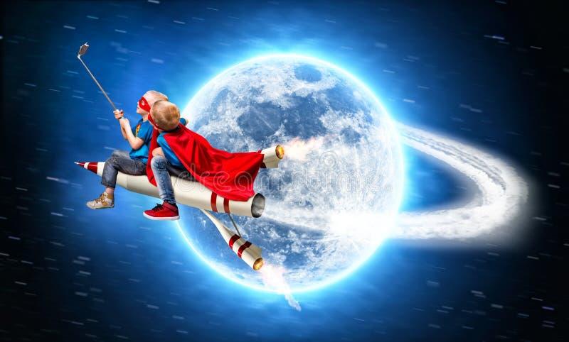 Los niños en trajes del super héroe vuelan en espacio en un cohete y tiran un selfie en un teléfono móvil imágenes de archivo libres de regalías