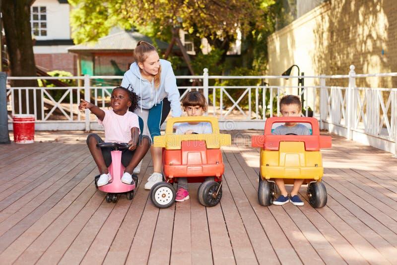 Los niños en una guardería conducen con los coches del pedal imagenes de archivo