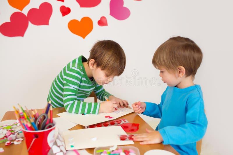 Los niños engancharon a los artes del día de tarjeta del día de San Valentín con los corazones foto de archivo libre de regalías