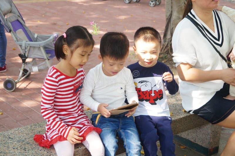 Los niños están jugando en las tabletas fotografía de archivo