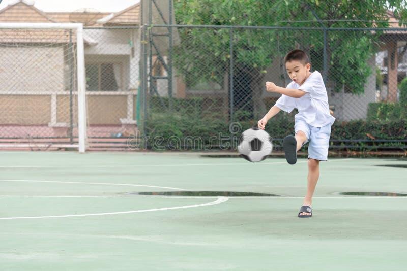Los niños están llevando los deslizadores que juegan a fútbol con el fondo borroso para mostrar el movimiento Para ejercitar desp imagen de archivo