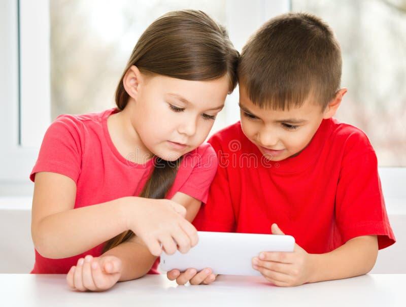 Los niños están utilizando la tableta imagen de archivo libre de regalías