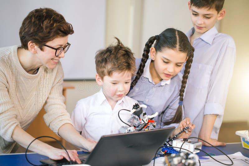 Los niños felices aprenden la programación usando los ordenadores portátiles en clases extracurriculares foto de archivo libre de regalías