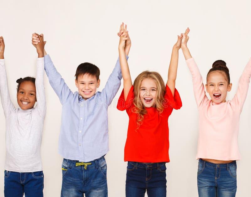 Los niños felices aumentaron las manos, colocándose en fila fotografía de archivo