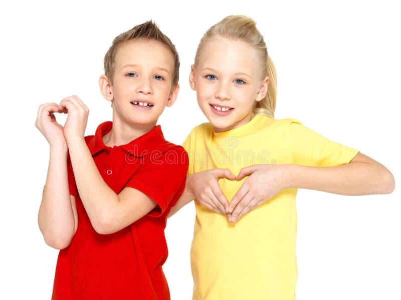 Los niños felices con una muestra del corazón forman fotos de archivo