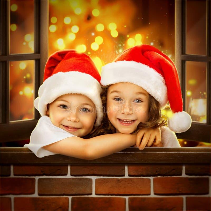 Los niños felices en el sombrero de Papá Noel miran hacia fuera la ventana imagen de archivo