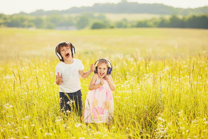 Los niños felices escuchan música en los auriculares imagen de archivo