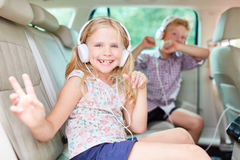 Los niños felices están cantando a la música en el coche imagen de archivo