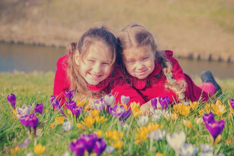 Los niños felices gozan de las flores de la primavera imágenes de archivo libres de regalías