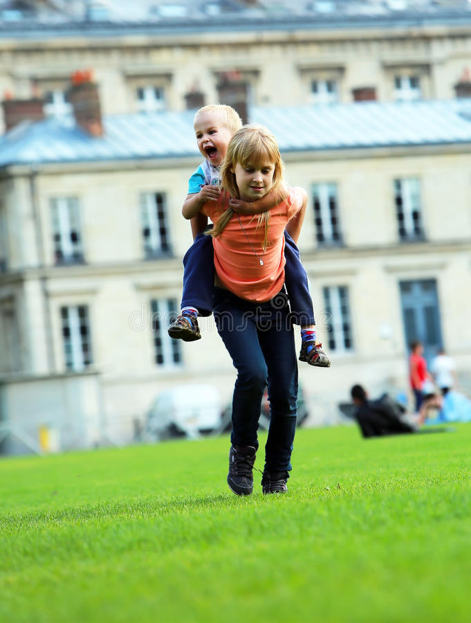 Los niños felices, la colegiala y su pequeño hermano en ciudad parquean imagenes de archivo