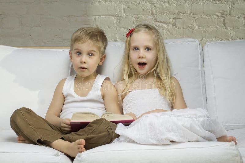 Los niños felices leyeron un libro fotos de archivo libres de regalías