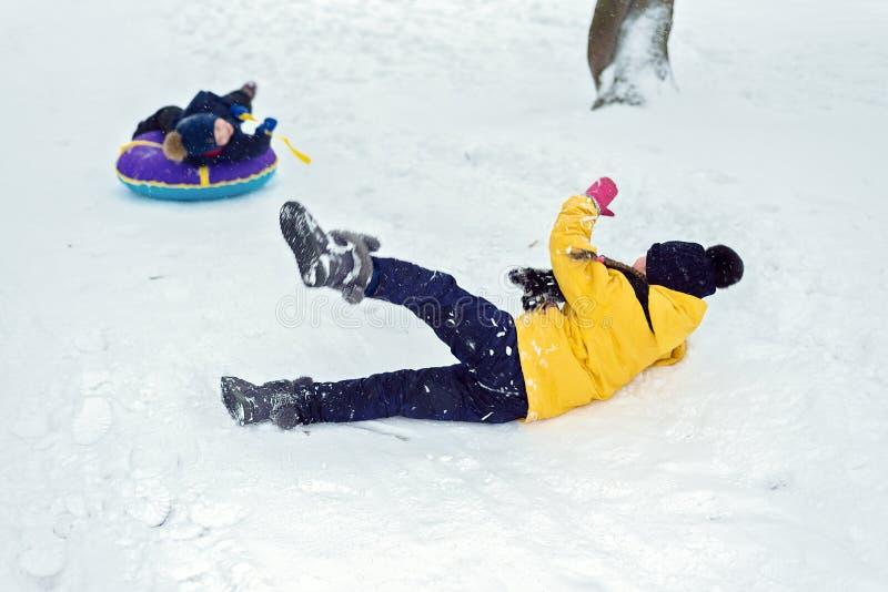 Los niños felices montan una diapositiva del invierno en un trineo Juego del hermano y de la hermana junto imagen de archivo