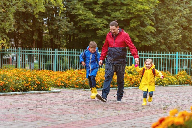 Los niños felices ríen, precipitación y funcionamiento a la escuela, vestida en impermeables, con una cartera detrás de una mochi foto de archivo libre de regalías