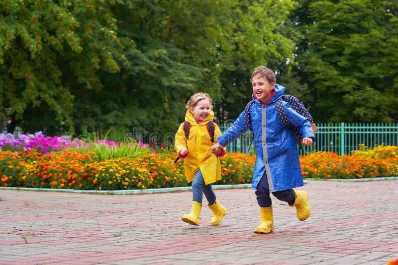 Los niños felices ríen, precipitación y funcionamiento a la escuela, vestida en impermeables, con una cartera detrás de una mochi imagen de archivo