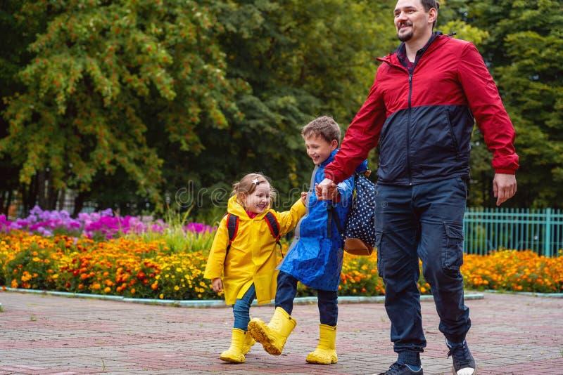 Los niños felices ríen, precipitación y funcionamiento a la escuela, vestida en impermeables, con una cartera detrás de una mochi fotos de archivo libres de regalías