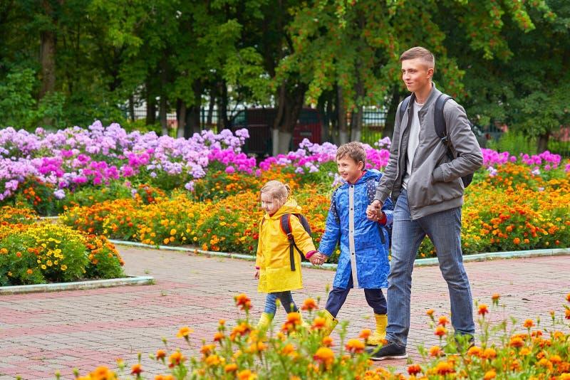 Los niños felices ríen, van a enseñar, vestido en impermeables, con una cartera detrás de una mochila fotografía de archivo
