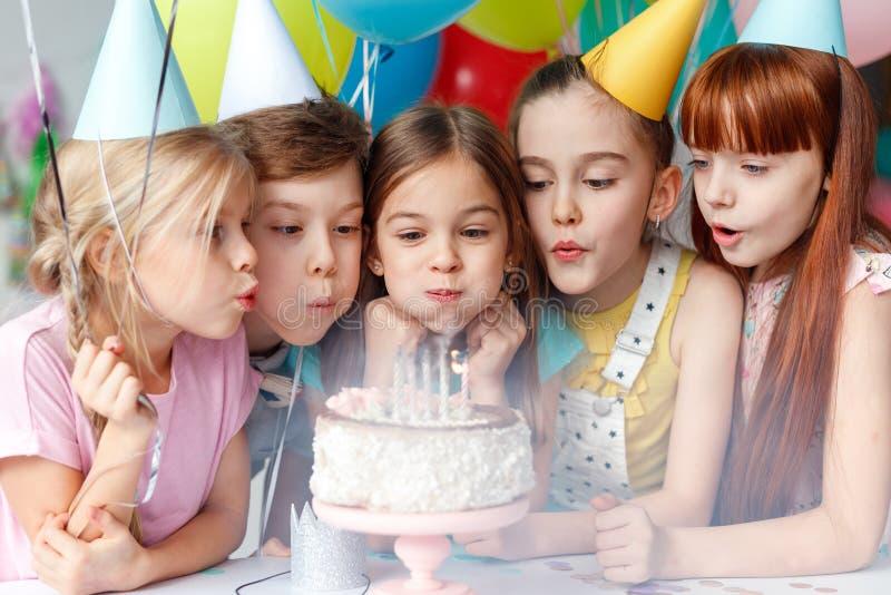 Los niños festivos en los casquillos del partido, velas del soplo en la torta deliciosa, hacen deseo, celebre el cumpleaños, tien imagenes de archivo