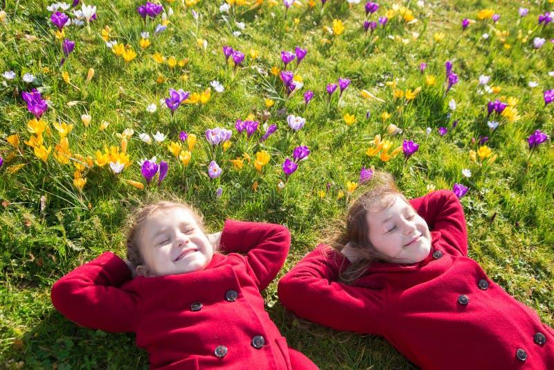 Los niños gozan de la primavera, del sol y de las flores fotografía de archivo