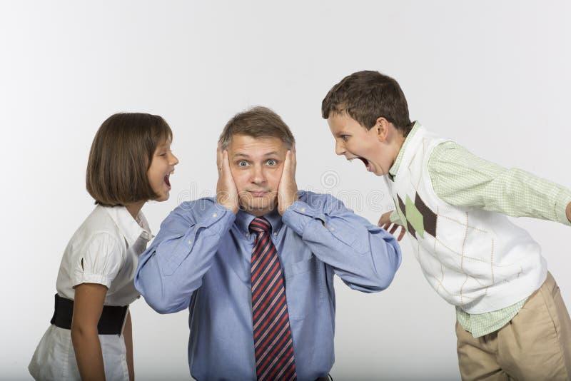 Los niños gritan en los oídos del papá imagen de archivo