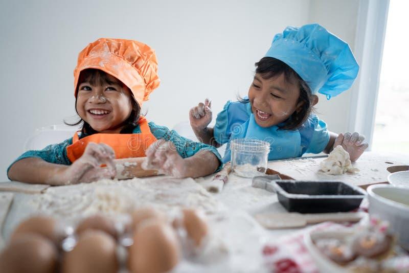 Los niños hacen alguna pasta y galletas juntas foto de archivo libre de regalías