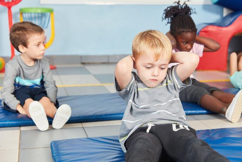 Los niños hacen ejercicio de los abdominales en el gimnasio foto de archivo libre de regalías
